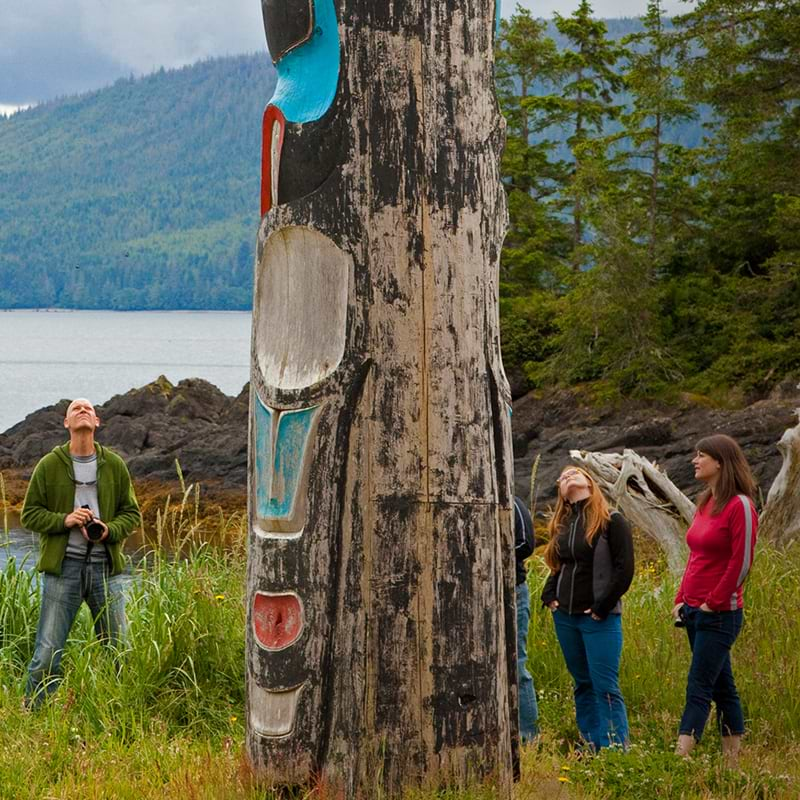 Group of students at Native Education College surrounding a totem pole