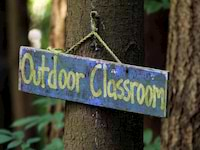 "A purple sign hanging from a tree with yellow writing reading ""Outdoor Classroom"""