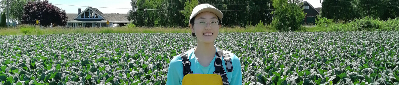 Co-op student Anika in front of a field of plants