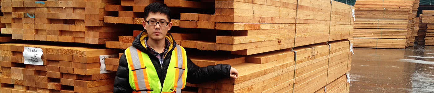 Co-op student Rui in front of processed wood products