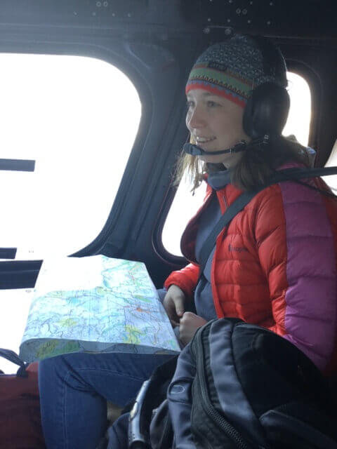 UBC Forestry Co-op Student, Audrey Standish, sits in a helicopter and holds a map.