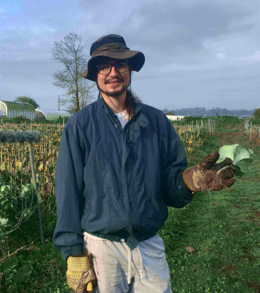 UBC Forestry Co-op Student Gregory Totaro holds a sunflower leaf.