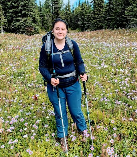 UBC Forestry Co-op student Hannah Bugas stands in a beautiful meadow with hiking sticks.