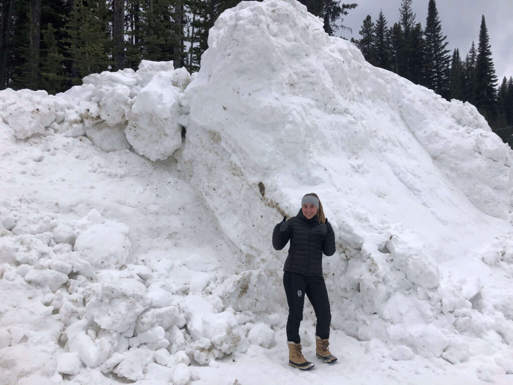 UBC Forestry Co-op Student Rachel Shanner is standing in front of an large hill of snow, with her thumbs up.