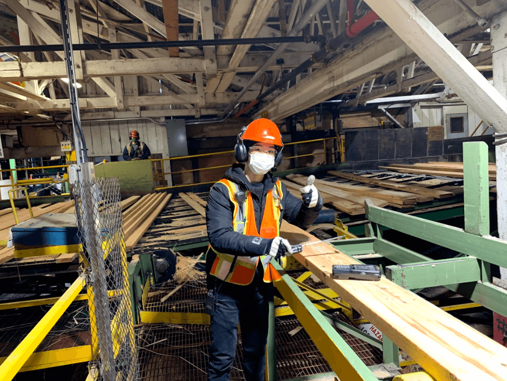 UBC Forestry Co-op Student Yu Luo stands by a plank of wood with her thumbs up.