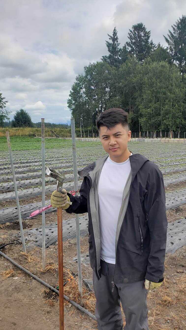 UBC Forestry Co-op student, Aaron Ng, is standing with a tool in a field.