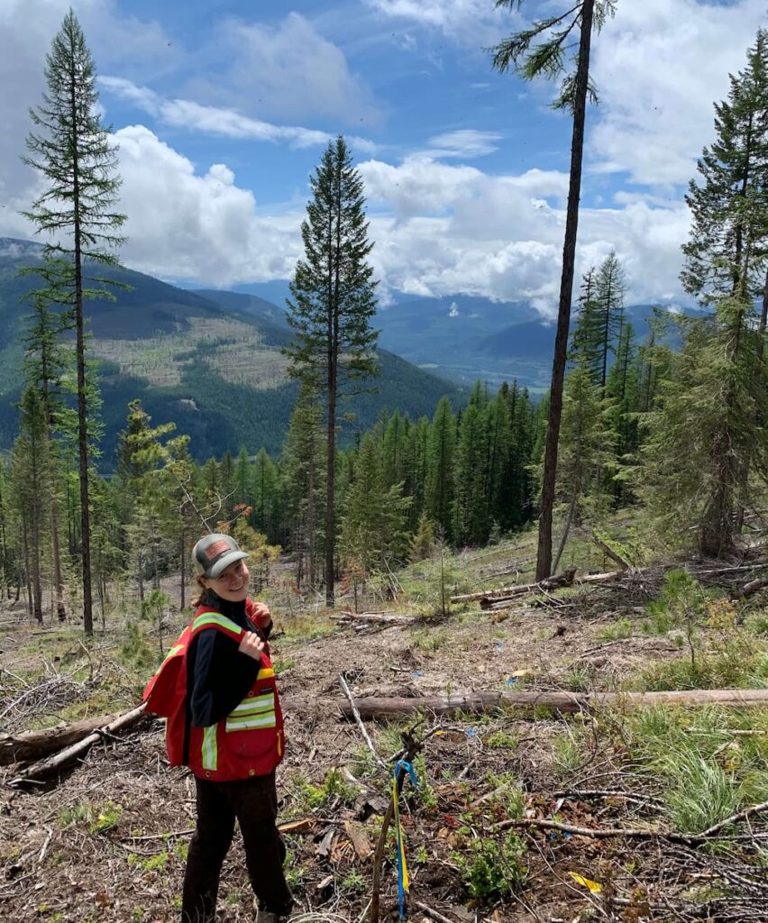 UBC Forestry Co-op Student, Ainsley Hannah, is standing in a forest.