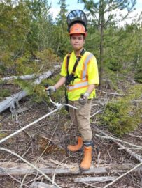 UBC Forestry Co-op student, Angelo Chang, is standing next to fallen wood with a tool in hand.