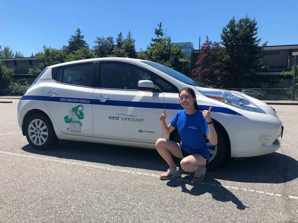 UBC Forestry Co-op student, Anika Ng, is sitting next to the West Vancouver Zero Emission Vehicle with her thumbs up.
