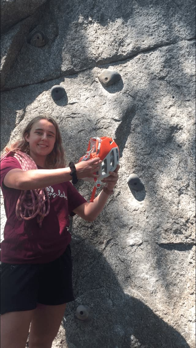 UBC Co-op Student Kelsey Bowman smiles next to a rock face with a helmet in her hands.