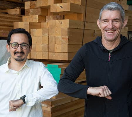 Dr Sadegh Mazloomi and Professor Phil Evans in the Centre for Advanced Wood Processing lab at UBC giving an elbow bump to each other.
