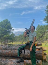 UBC Co-op student, Abigail Herman, is holding a chainsaw, standing on top of cut trees, and smiling.