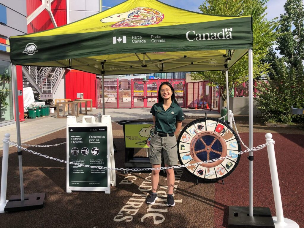 UBC Forestry Co-op Student, An Hoang, is standing and smiling in front of a Parks Canada booth.