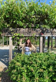 UBC Forestry Co-op student, En Jung Hwang, stands in front of the Sharing Farm's sign.