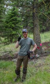UBC Forestry Co-op student Jonathan Garsson stands in the forest with equipment in his hands and smiles.
