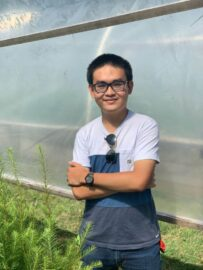 UBC Forestry Co-op student, Le Nguyen Dao, stands in front of a forest view.