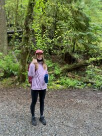 UBC Forestry Co-op student, Serena Sturton, smiles with her thumbs up in front of a forest.