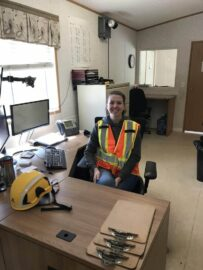 UBC Forestry Co-op student, Zoe Pazurik, is sitting at a desk with safety clothing on, while smiling.